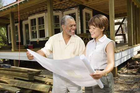 Couple holding blueprints on construction site.  Horizontally framed shot. photo
