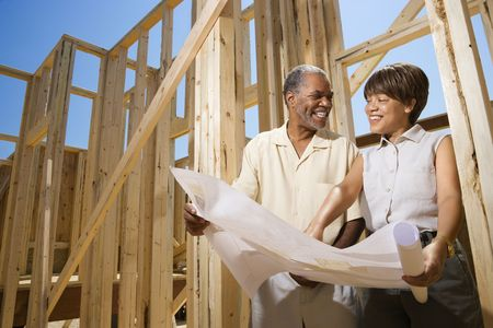 building material: Couple holding blueprints beside construction framing.  Horizontally framed shot.