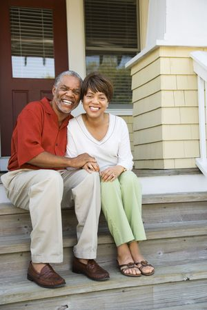 coppia in casa: Coppia seduta sulla scalinata esterna della casa sorridente. Colpo verticalmente con cornice. Archivio Fotografico