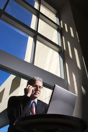 Businessman with a laptop computer talking on cellphone and sitting in front of large windows. photo