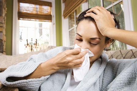 sick: Mujer joven enferma sopla su nariz en un tejido. Horizontal de disparo.