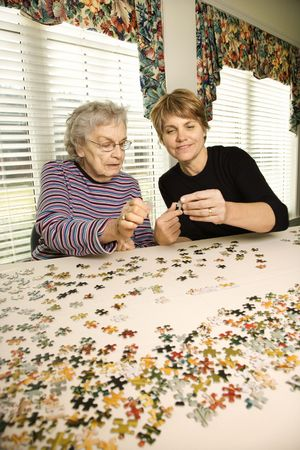 Elderly woman and younger woman work on a jigsaw puzzle together.  Vertical shot. photo