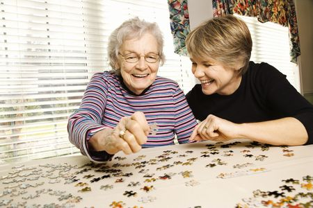 senior citizens: Elderly woman and a younger woman work on a jigsaw puzzle.  Horizontal shot. Stock Photo