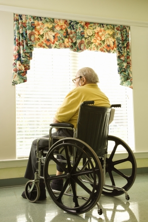 Elderly man in wheelchair sits and looks out of large window. Vertical shot. photo
