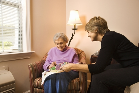 senior living: Older woman does needlepoint while another woman watches. Horizontal shot. Stock Photo