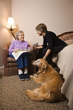 pet therapy: Elderly Woman in her bedroom does needlepoint with a younger woman and a dog in the room. Vertical shot. Stock Photo