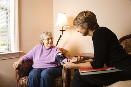 assisted living: Nurse checks an elderly womans blood pressure in an assisted living home.  Horizontal shot.