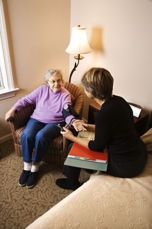 assisted living: Nurse checking an elderly womans blood pressure in assisted living home. Vertical shot.