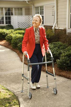 Oudere lachende vrouw neemt een wandeling buiten met haar walker.  Verticaal schot.