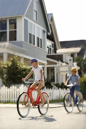 residential neighborhood: Two teens ride bicycles through a residential neighborhood. Vertical shot.