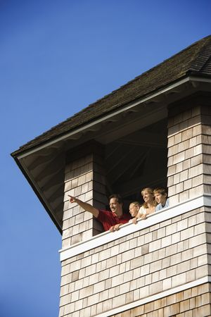 Low angle view of a family looking and pointing out a tower window. Vertical shot. photo
