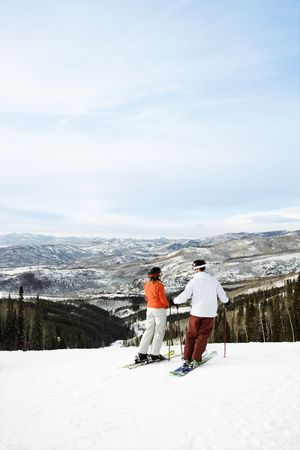 Rear view of skiers on ski slope with mountains in background. Vertical shot. photo