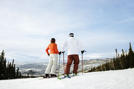 colorado: Rear view of skiers on ski slope with mountains in background. Horizontal shot.