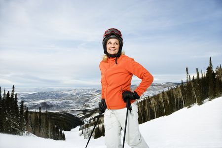 Smiling skier on ski slope in Colorado leaning on her poles with mountains in background. Horizontal shot. photo