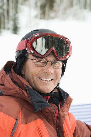 Smiling male skier wearing red goggles and orange ski jacket. Vertical shot. photo