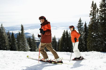 winter escape: Side view of skiers on a snowy ski slope with trees and valley in background. Horizontal shot.