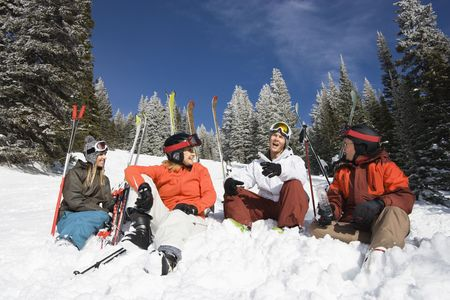 winter sports: Group of male and female skiers sitting in the snow relaxing talking and smiling. Horizontal shot.