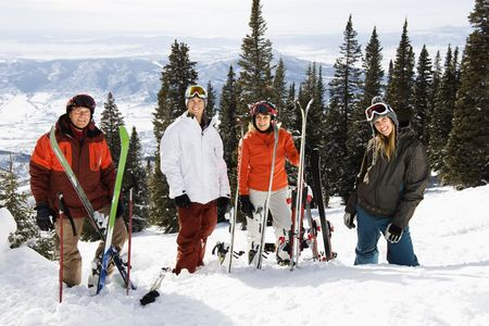 Portrait of group of skiers standing on ski slope in Colorado smiling with a valley in background photo