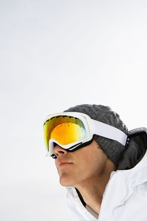 Head shot of a male skier wearing ski goggles against a snowy white background. Vertical shot. photo