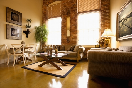 condominium: Interior of furnished living room with large windows and brick wall. Horizontal shot. Stock Photo