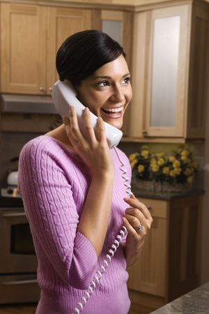 house call: Smiling woman has an enjoyable telephone conversation in the kitchen.  Vertical shot.