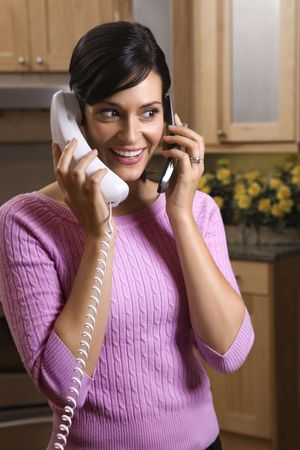 Smiling woman multitasks between her cell phone and landline telephones. Vertical shot. photo
