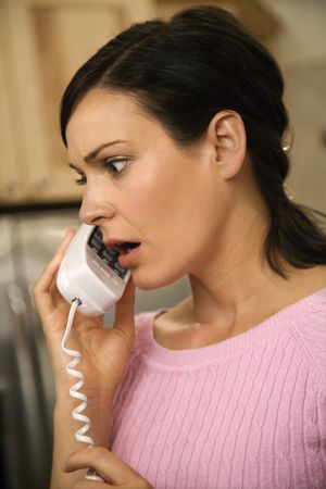 Woman with serious expression talking on telephone.  Vertical shot. photo