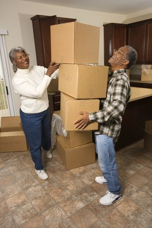 home moving: Smiling senior african american man balancing moving boxes while his wife helps. Vertical shot.