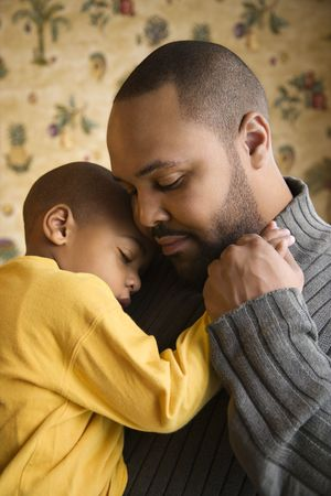 fatherhood: Affectionate young african-american father holds young son to his chest.  Vertical shot.