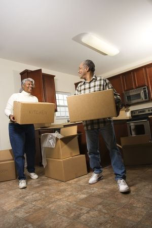 Smiling senior african american man and woman carry moving boxes into a new home.  Vertical shot. photo