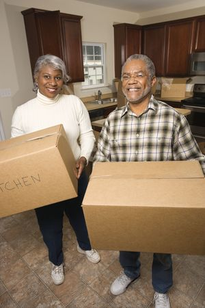 buying: Portrait of smiling senior african american man and woman with moving boxes in a new home.   Vertical shot.