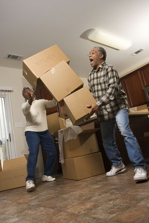 storage boxes: Senior african american man dropping stacked moving boxes while his wife attempts to catch them.