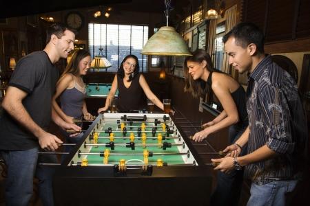 socializando: Grupo de j�venes hombres y mujeres que goza de una partida de futbol�n en un bar.  Horizontal de disparo.