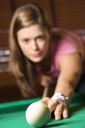 Young woman concentrating while shooting pool. Vertical shot. Stock Photo - 6302401