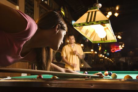 horizontal bar: Young woman playing billiards with a young man in the background.  Horizontal shot. Stock Photo