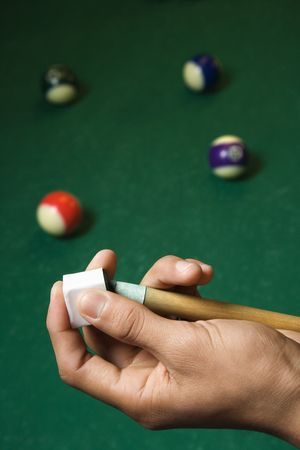 Hand chalking a pool cue with a billiards table in background. Vertical shot. photo