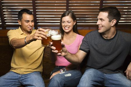 Three smiling young adult friends sitting on a bench toasting with their beers. Horizontal shot. photo
