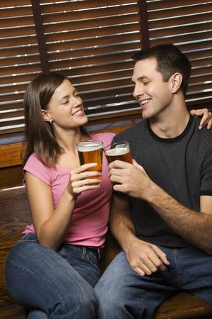 socialize: Young man and woman sitting together toasting their beers while relaxing at a pub. Vertical shot. Stock Photo