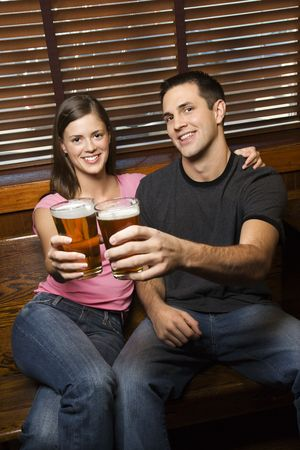 Young man and woman sitting together toasting their beers at pub looking at viewer. Vertical shot. photo