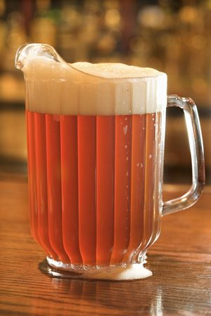 Full beer pitcher with foam on a bar counter. Vertical shot.