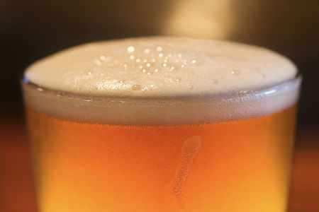 foaming: Close-up of glass of beer with foam on top. Vertical shot. Stock Photo