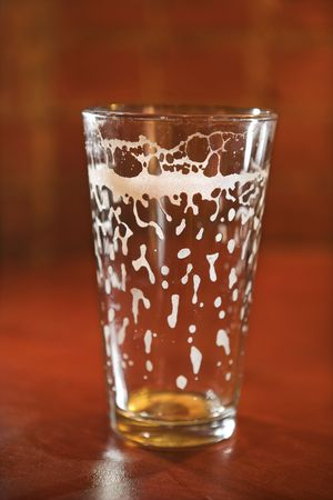 empty: Empty beer glass on bar counter with residual foam lining the glass. Vertical shot. Stock Photo