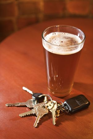 dwi: Car keys lying next to a full glass of beer.  Vertical shot. Stock Photo
