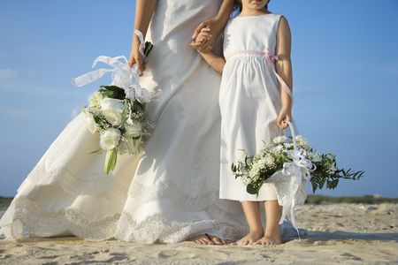 milestones: Bride and young flower girl stand on the sandy beach holding hands. Horizontal shot.