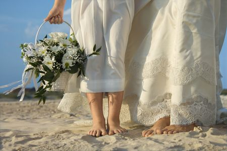 Bride and flower girl stand on a sandy beach. Horizontal shot. photo