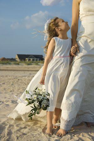 Flower girl looks up towards a bride on a sandy beach. Vertical shot. photo