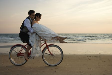 driven: Bride rides the handle bars of a bicycle being driven by her groom on beach. Horizontal shot. Stock Photo