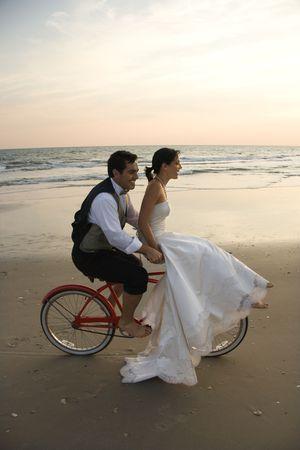 handle bars: Novia paseos en las barras de control de una bicicleta de ser controlado por su novio en la playa. Un disparo vertical.