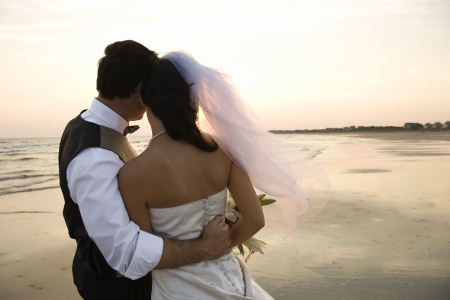 woman beach dress: Rear view of a newlywed couple hugging on beach. Horizontal shot. Stock Photo