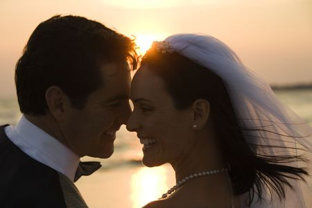 woman beach dress: Newlyweds with their heads together in front of a setting sun on the beach. Horizontal shot. Stock Photo